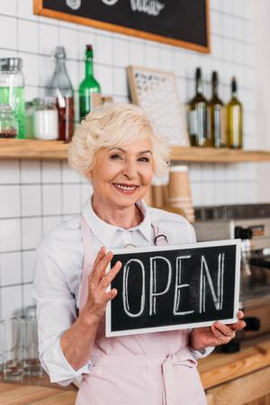 portrait of smiling senior worker in apron holding open chalkboard in hands in coffee shop