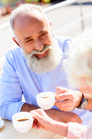 partial view of happy senior couple drinking coffee together Banco de Imagens