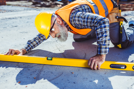 Bearded worker in reflective vest and hardhat working with spirit level at construction site, leveling the floor Stock Photo - 102611744