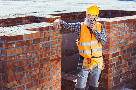 Construction worker in reflective vest and hardhat leaning on unfinished wall and talking on portable radio 写真素材