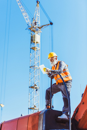 Smiling worker in reflective vest and hardhat using digital tablet while standing on top of excavator cabin Stock Photo