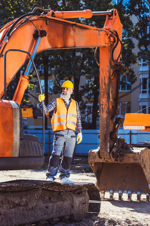 Worker in reflective vest and hardhat standing in front of excavator at construction site