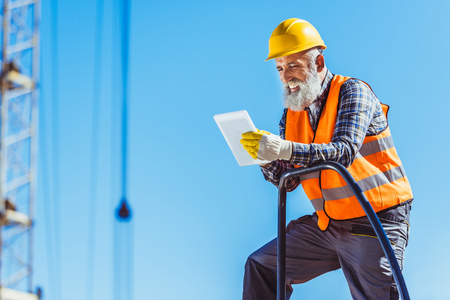 Smiling worker in reflective vest and hardhat using digital tablet