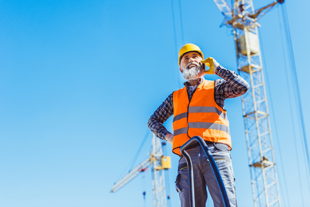 Smiling construction worker in reflective vest and hardhat talking on smartphone Stock Photo - 102597851