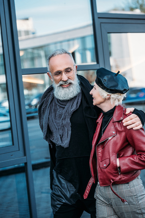 portrait of stylish senior man and woman walking on street together