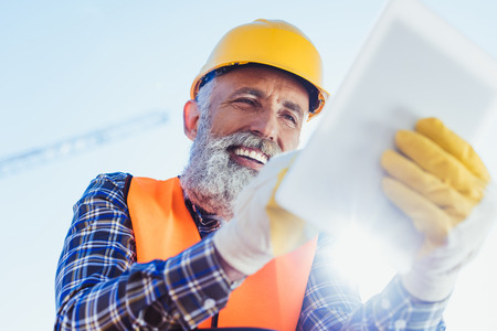 Cheerful construction worker in reflective vest and hardhat using digital tablet