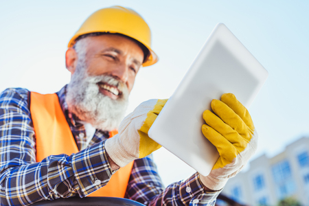 Smiling construction worker in reflective vest and hardhat using digital tablet