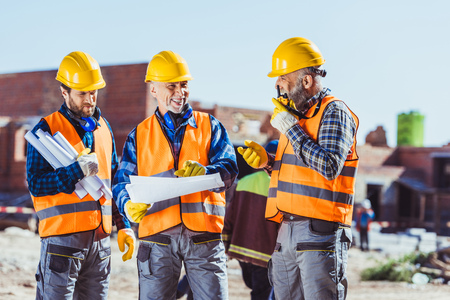 Three workers in hardhats examining building plans and talking on portable radio at construction site