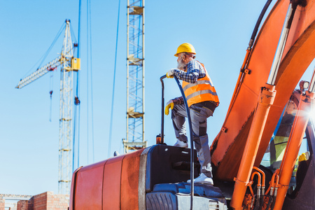 Worker in reflective vest and hardhat standing on top of excavator cabin with cranes in the background