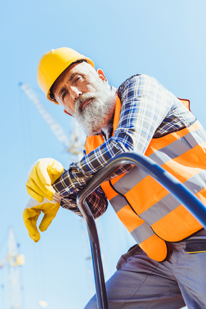 Bearded construction worker in reflective vest and hardhat leaning on guardrail and looking at camera