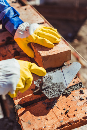 Cropped shot of construction worker in protective gloves laying bricks using spatula