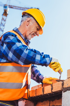 Construction worker in reflective vest and hardhat laying bricks using spatula