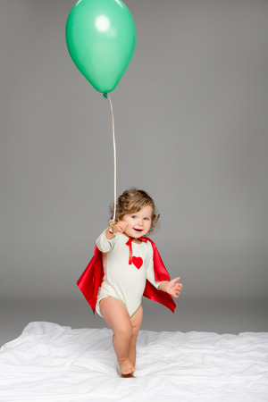 happy toddler in superhero cape holding balloon isolated on grey
