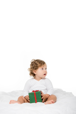 adorable toddler girl with wrapped present in hands looking away isolated on white