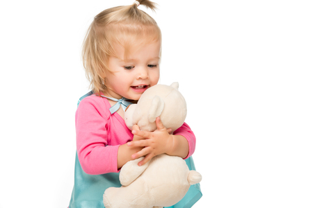 portrait of toddler girl in superhero cape holding teddy bear isolated on white