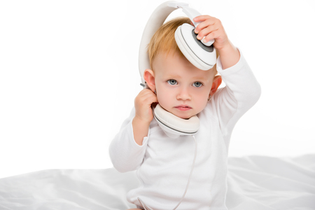 portrait of cute caucasian baby with headphones on head looking away isolated on white