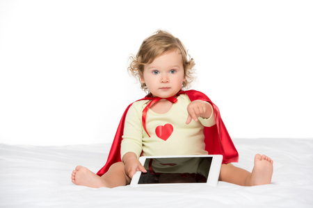 adorable toddler in superhero cape with tablet pointing isolated on white