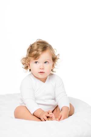 cute toddler girl holding feet and looking away isolated on white
