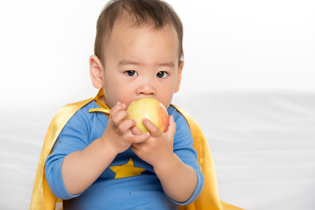 portrait of cute asian toddler in superhero cape eating fresh apple isolated on white Фото со стока