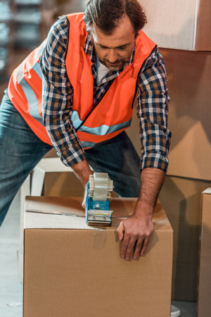 male warehouse worker packing box with adhesive tape