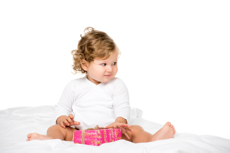 cute toddler girl with wrapped present looking away isolated on white