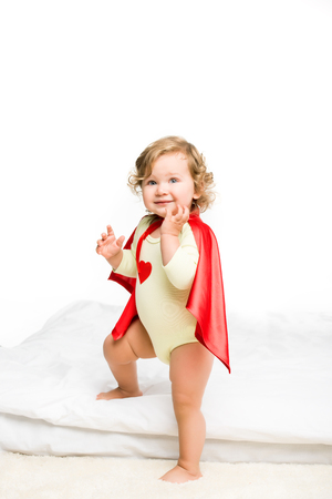 adorable toddler girl in superhero cape isolated on white