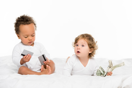 multiethnic toddlers holding money and credit cards isolated on white Stock Photo