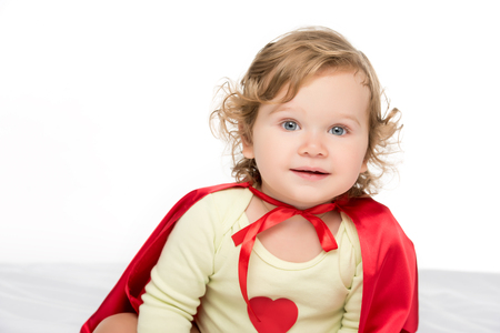 portrait of adorable toddler girl in superhero cape isolated on white
