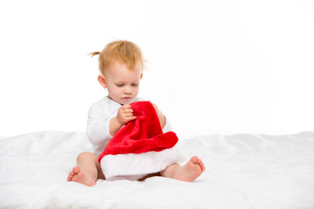 focused baby girl looking at santa hat in hands isolated on white