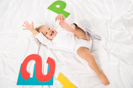 overhead view of happy baby with paper letters lying on bed Stock Photo