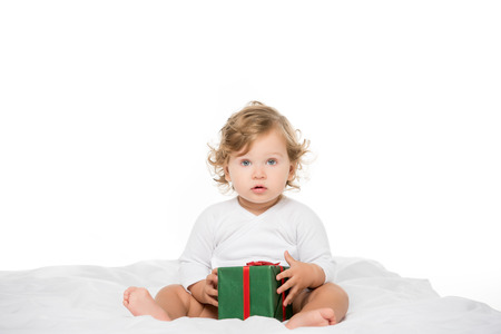 adorable toddler girl with wrapped present in hands looking at camera isolated on white Stock Photo