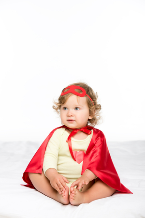 pretty toddler girl in superhero costume isolated on white