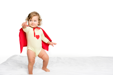 adorable toddler girl in superhero cape pointing at camera isolated on white