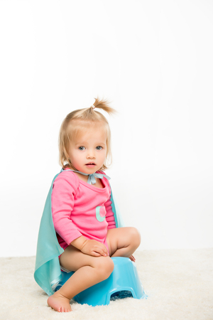 adorable toddler girl in superhero cape sitting on pottie isolated on white