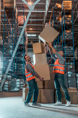 full length view of two workers in vests holding boxes in warehouse