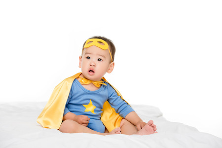 cute asian toddler boy in superhero costume isolated on white