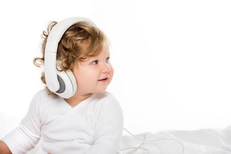 portrait of smiling toddler listening music in headphones isolated on white