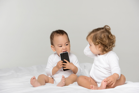 multicultural toddlers with digital smartphone isolated on grey