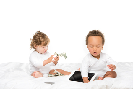 multicultural toddlers with cash and digital tablet isolated on white