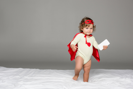 adorable toddler girl in superhero costume with smartphone isolated on grey Stock Photo