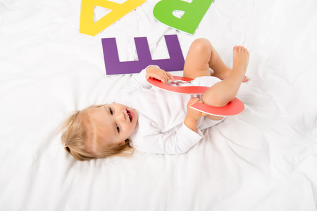 side view of happy baby with paper letter lying on bed