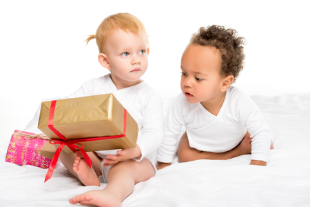 cute multiethnic toddlers with wrapped gifts isolated on white Stock Photo