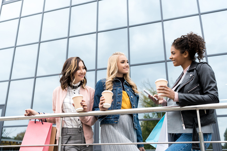 group of young women with shopping bags and coffee to go talking outdoors near mall
