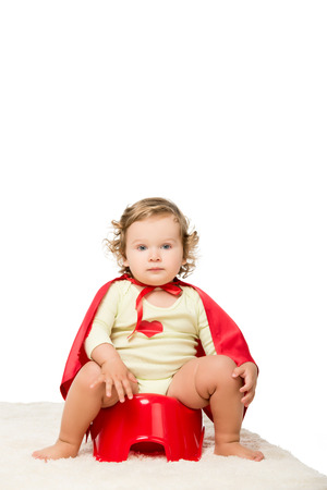 toddler in superhero cape sitting on pottie isolated on white Stock Photo