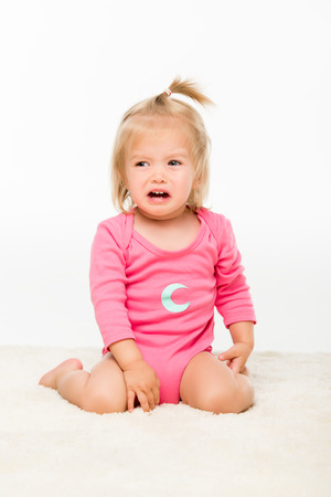 portrait of crying toddler girl in bodysuit looking away isolated on white Stock Photo