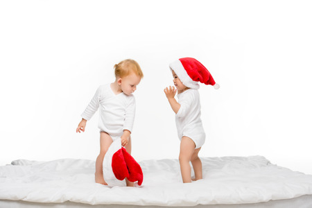 toddler asian boy and caucasian girl with santa hats isolated on white Stock Photo