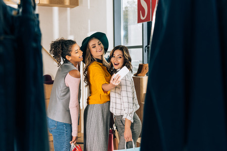 group of happy young women taking selfie in clothing store Stock Photo