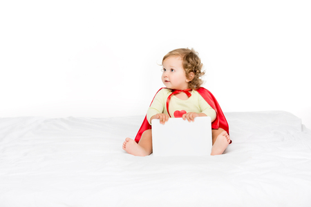 cute toddler in superhero cape with tablet in hands looking away isolated on white