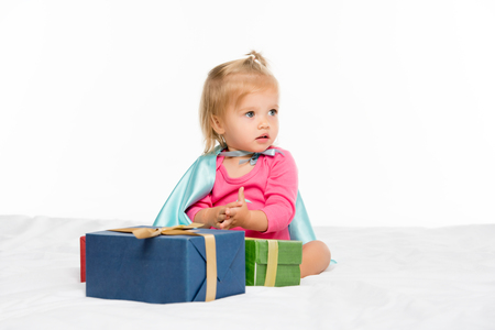 portrait of adorable baby in superhero cape with wrapped gifts isolated on white
