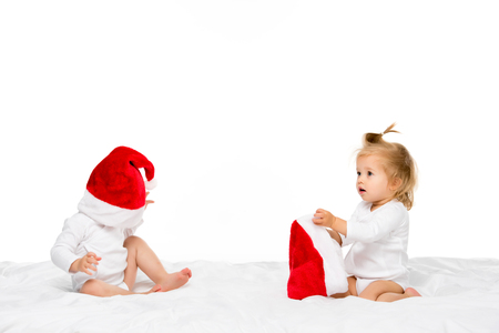 cute toddlers in santa hats isolated on white